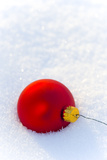 Close-Up of a Red Christmas Bauble on Snow Photographic Print by Bjorn Andren