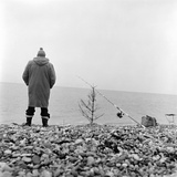A Man Fishing on a Shingle Beach in Kent, with His Fishing Rod Propped on a Bare Christmas Tree Stampa fotografica di John Gay