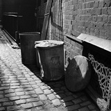 Three Dustbins in a Cobbled London Back-Street, Beside an Ornate Iron Wall Grating Photographic Print by John Gay
