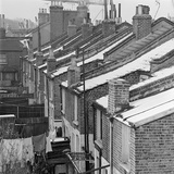 A View from Roof Level Along the Snowy Roofs of a Line of Terraced Brick Houses Photographic Print by John Gay