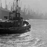 London Docks, the Tug Plasma in the Foreground Departing across the Water Photographic Print by John Gay
