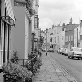 A Street with a Row of Different Sized Terraced Houses and Cars Parked Photographic Print by John Gay