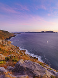 Spain, Galicia, Cangas, Yacht Sailing in Sea at Dusk Photographic Print by Shaun Egan