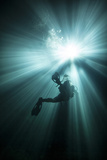 A Scuba Diver Ascends into the Light Emanating Above Posters