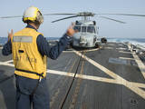 Boatswainâs Mate Signals to the Pilot of an Mh-60R Sea Hawk Photographic Print