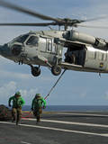 Airmen Run to Cover after Attaching Cargo Legs to an Mh-60S Sea Hawk Photographic Print