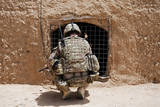 Soldier Searches a Compound in Afghanistan Photographic Print