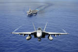 An F-A-18E Super Hornet Flying Above USS John C. Stennis Photographic Print