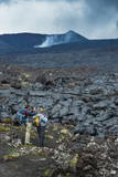 Tourists Standing at a Cold Lava Stream after an Eruption of Tolbachik Volcano Photographic Print by Michael Runkel