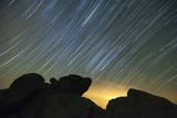 Light Pollution Illuminates the Sky and Star Tails Above Large Boulders Photographic Print