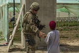 U.S. Army Soldier Greets an Afghan Child Photographic Print