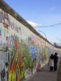 Couple Walking Along the East Side Gallery Berlin Wall Mural, Berlin, Germany, Europe Photographic Print by Simon Montgomery