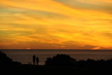A Couple Enjoys the Sunset over the Pacific Ocean Photographic Print by Mike Nelson
