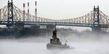 A Tug Boat Passes Along a Fog Shrouded the East River and the Ed Koch Queensboro Bridge in New York Photographic Print by Justin Lane
