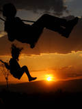 Silhouette of Girls on Swings During the Sunset Photographic Print by Georgi Licovski