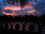 Wagon Wheels are Silhouetted as the Sun Sets Photographic Print by Barbara Walton