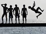 Boys Jumps into the Water on the First Sunny Spring Day in Malmo Photographic Print by Johan Nilsson