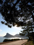 A Cyclist Rides Past the Sentinel Peak in Hout Bay Near Cape Town, South Africa Photographic Print by Jon Hrusa