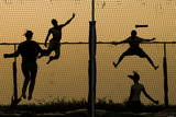 Senegalese Boys and Girls Jump on Trampolines at Sunset in Dakar, Senegal Photographic Print by Nic Bothma