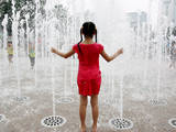 A Child Enjoys a Cool Splash in a Fountain, Seoul City, South Korea Photographic Print by Jeon Heon-Kyun