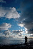 Dark Clouds Appear as an Angler Tries to Get an Early Catch Photographic Print by Stefan Sauer