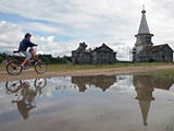 A Girl Rides a Bicycle Passing by Abandoned Orthodox Wooden Church Photographic Print by Sergei Chirikov