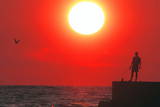 A Fisherman Is Silhouetted in Front of the Sunset on the Black Sea in Front Sochin Photographic Print by Sergei Ilnitsky