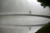 A Cyclists Rides His Bike over a Bridge at the Karlsaue Park in Kassel, Germany Photographic Print by Uwe Zucchi