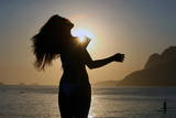 A Woman Is Silhouetted Against the Sunset on Arpoador Beach in Ipanema Photographic Print by Marcelo Sayao