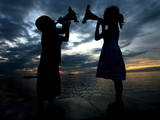 Two Children Sound their Toy Trumpets Along the Manila Baywalk in Manila, Philippines Photographic Print by Mike F. Alquinto