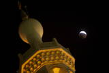 The View of a Partial Lunar Eclipse Above the Mosque in Sharjah East of Dubai Photographic Print by Ali Haider