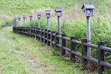 Japan, Nara Prefecture, Soni Plateau. Wooden lanterns along a fence. Photographic Print by Dennis Flaherty