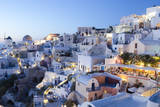 Greece, Santorini, Oia. white buildings and steep mountains at sunset. Fotodruck von Bill Bachmann