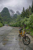 Bicycle sits in front of the Guilin Mountains, Guilin, Yangshuo, China Photographic Print by Josh Anon
