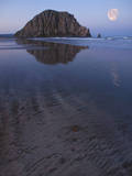 USA, California. Morro Rock reflecting in wet sand at moonrise. Photographic Print by Anna Miller