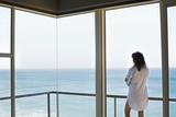Rear View of Young Woman Looking at Ocean View from Balcony at Resort Photographic Print by  Nosnibor137