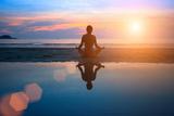 Silhouette Young Woman Practicing Yoga on the Beach at Sunset Fotodruck von De Visu