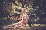 Dreaming Blond Retro Woman with a Book Sitting on a Meadow Photographic Print by NejroN Photo