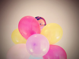 A Pretty Girl Hiding Behind a Bunch of Balloons Photographic Print by  graphicphoto