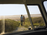 Full Length of Loving Young Couple Walking Towards Beach View from Campervan Window Photographic Print by  Nosnibor137