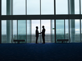 Side View of Two Silhouette Businessmen Shaking Hands in the Airport Lobby Photo by  Nosnibor137