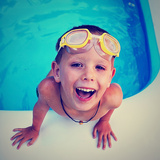 A Young Boy Swimming in a Small Pool Photographic Print by  graphicphoto