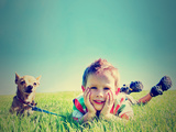 A Boy and a Tiny Chihuahua in the Grass Posters by  graphicphoto