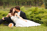 Wedding, Beautiful Young Bride Lying Together with Groom in Love on Green Grass Kissing Photographic Print by  khorzhevska