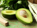 Ripe Avocado Cut in Half on a Wooden Table Photographic Print by Olga Krig