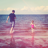 Father and Little Girl Playing in Water at Beach Photo by  melking