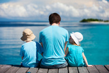 Back View of Father and Kids Sitting on Wooden Dock Looking to Ocean Photographic Print by BlueOrange Studio