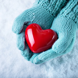 Woman Hands in Light Teal Knitted Mittens are Holding a Beautiful Glossy Red Heart Photographic Print by  smaglov