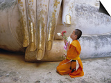 Novice Buddhist Monk Kneeling Beneath the Phra Atchana Buddha Statue, Sukhothai Province, Thailand Print by Gavin Hellier