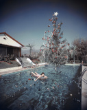Rita Aarons, wife of photographer Slim Aarons, swimming in a pool festooned with floating baubles. Premium Photographic Print by Slim Aarons